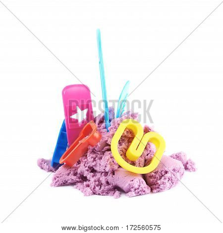 Pile of kinetic sand with the plastic letter molds over it, composition isolated over the white background