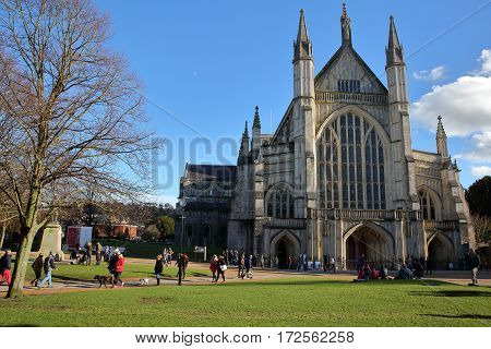 WINCHESTER, UK - FEBRUARY 4, 2017: Exterior view of the Cathedral with people enjoying a sunny winter day