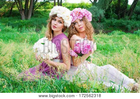 portrait of two young beautiful curly women in the peony wreath outdoor on green background