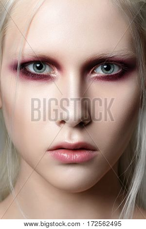 Beauty portrait of young woman with white brows and hair. Perfect skin and fashion makeup. Red smokey eyes. Studio shot. Sensuality passion trendy youth makeup concept.