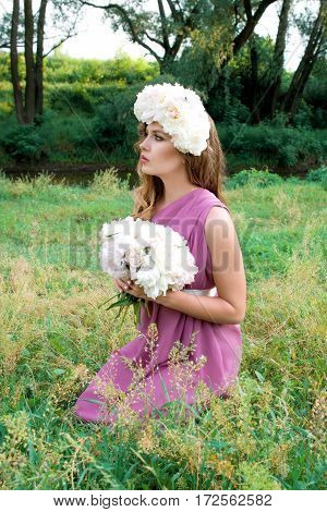 portrait on young beautiful curly woman in the peony wreath outdoor on green background