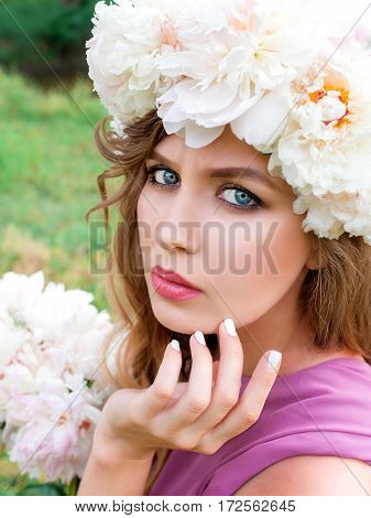 portrait on young beautiful curly woman with white nails in peony wreath outdoor on green background