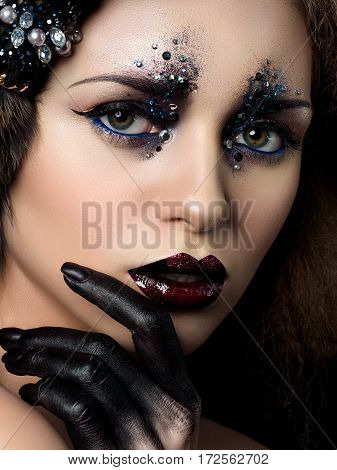 Beauty portrait of young woman with fashion makeup with rhinestones. Black hand and dark red lips. Studio shot.