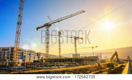 Large construction site including several cranes working on a building complex with clear blue sky and the sun