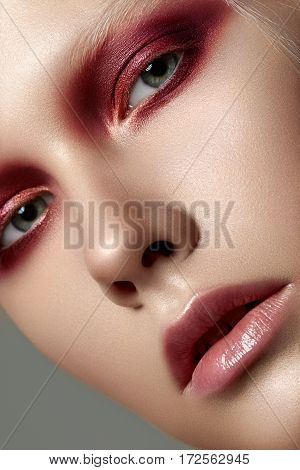 Close up beauty portrait of young woman with white brows and red smokey eyes. Perfect skin and fashion makeup. Studio shot. Sensuality passion trendy youth makeup concept.