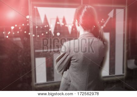 Graph against businesswoman looking through window