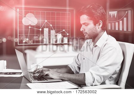 Digital generated image of graph charts against businessman working on laptop