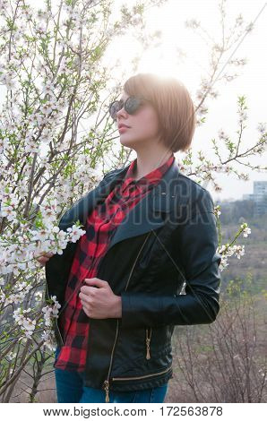 Fashion portrait of young pretty brunette model in cool sunglasses, wearing trendy spring jacket against white blooming tree background.