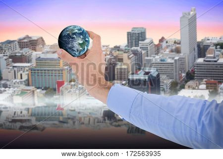 Businessman holding little earth in presentation against view of crowded buildings in city