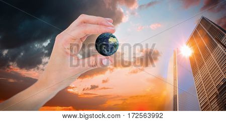 Woman presenting little earth with her hand against orange and blue sky with clouds