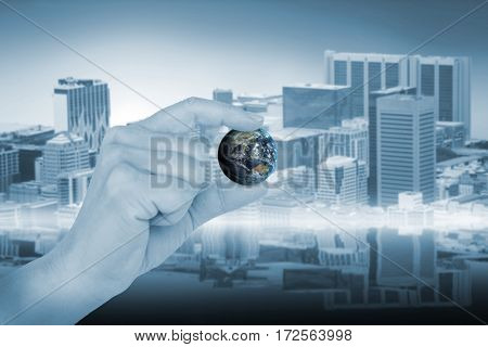Close-up of gesturing hand against towers and building in city