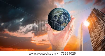 Hand presenting little earth against orange and blue sky with clouds
