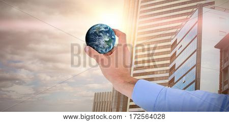 Businessman holding little earth in presentation against sky