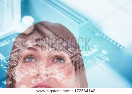 Close up of woman looking up against computer chip in circuit board