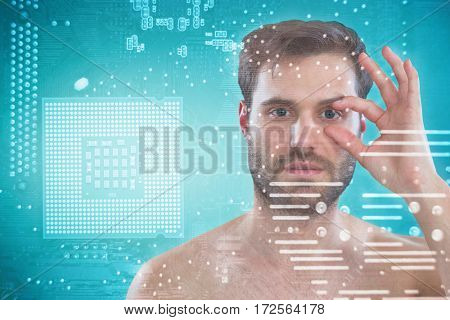 Shirtless man opening his eye with fingers against micro parts in computer chip