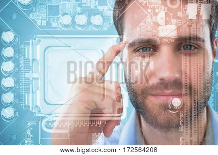 Man with finger pointing to head against close-up of circuit board