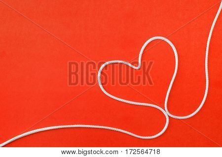 Heart shape made of rope on red background