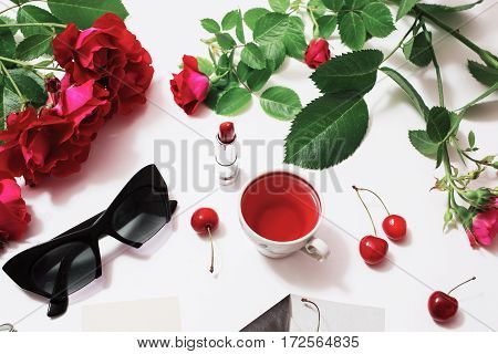 Frame of red beautiful roses with green leaves lady lipstick red tea black glasses a ring with a black stone envelope ripe cherries and a leaf of paper lie on a white background. Flat lay art