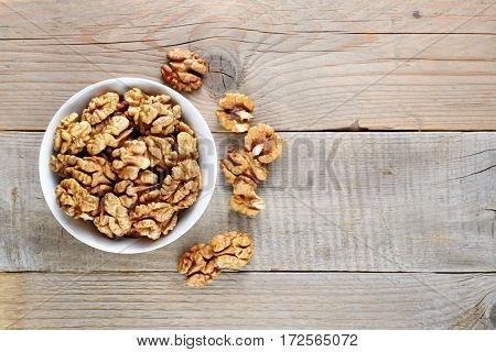 Walnuts in bowl on wooden table top view
