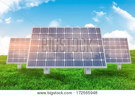 Solar panel against green field under blue sky