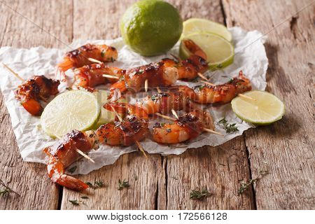 Tiger Prawns Wrapped In Bacon On Skewers With Thyme And Lime Close Up. Horizontal