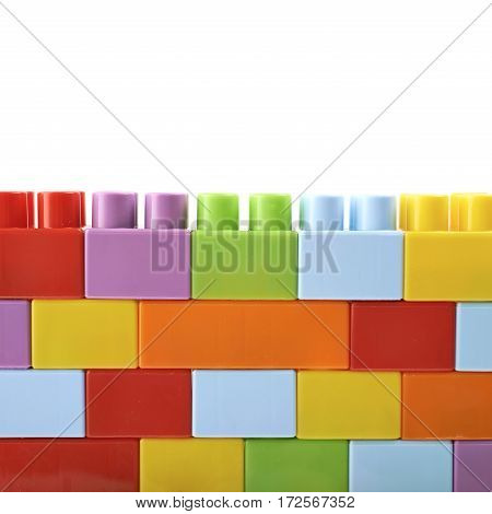 Wall made of plastic construction toy bricks isolated over the white background