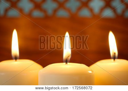 Macro of three burning candles against brown indian wooden background