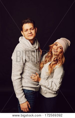 Cheerful couple in winter clothes hugging and kissing. Process with VSCO S3 preset