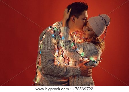 Cheerful couple in winter clothes hugging and kissing. Process with VSCO S3 preset. Low light