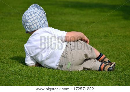 Little child lies sideways in the green meadow