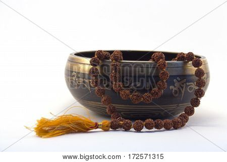 Tibetan singing bowl with engraved mantra and rudraksa side view on white background 2