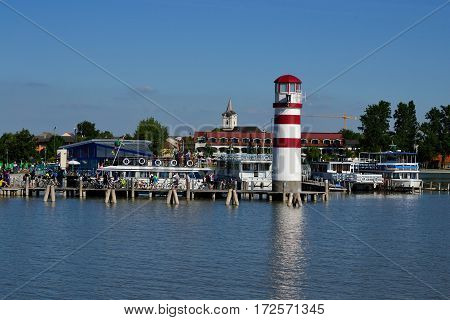 Boat landing stage in Podersdorf with lighthouse and church - austria