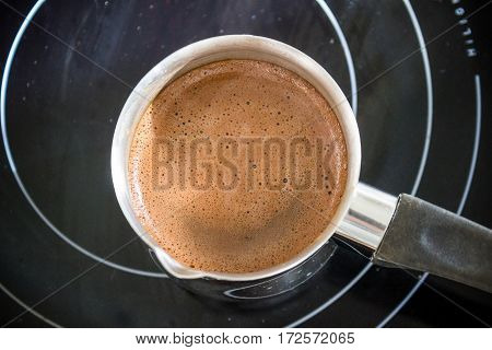 Hot cacao drink in pot on electric stove. Domestic kitchen recipes.