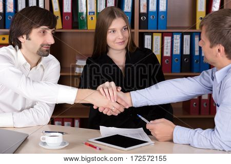 Three Business People Men and Lady shaking Hands after reaching a Deal in Office Interior with many color Document Folders on Background Focus on Beautiful Lady Face.