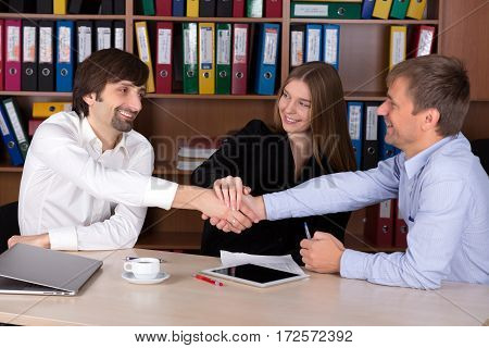 Three Business People Men and Lady shaking Hands after reaching a Deal in Office Interior with many color Document Folders on Background Focus on Happy Face of Lady.