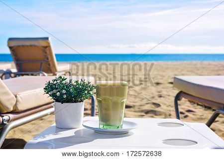Latte at the beach. Iced Coffee Frappuccino or frappe in a tall glass. Sea view background Barcelona Catalunya Spain
