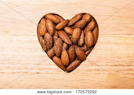 Whole food good for health. Heart shaped almonds on wooden surface board background