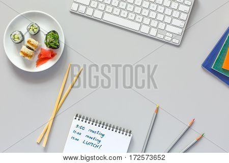 Top View of Office Work Place on grey Table with Computer Pencils Documents and Sushi Set with wooden Chopsticks on Table Hand writing in Opened Notepad with Business Schedule with Meetings and Lunch.