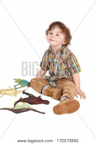 Happy three year old boy sitting on the floor playing with his toy dinosaurs isolated for white background.