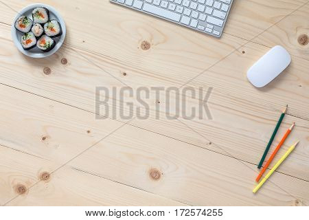 Image of Light Wooden Table with Business and Hobby Items and Sushi Set Computer Keyboard Color Pencils from above