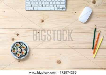 Natural handcrafted wooden Table in light brown color with Computer and other Electronics and some Stationery and Set of Sushi on Desk