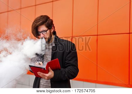 Young hipster man with a beard and glasses smokes an electronic cigarette. He holds a tablet pc. Youth fashion. Delicious pairs. Man makes startup. Business on the Internet.