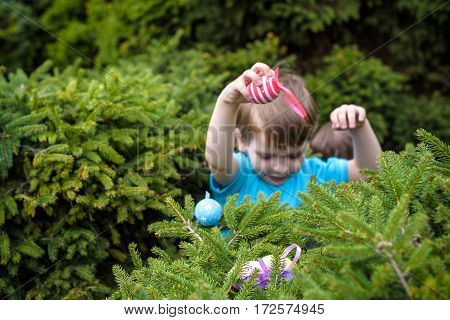 Little Boy Hunting For Easter Egg In Spring Garden On  Day. Cute  Child With Traditional Bunny Celeb