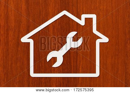 Paper house with wrench spanner inside on dark wooden background. Housing repair concept. Abstract conceptual image