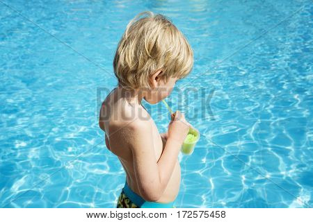 Boy drinks ice from juice at the pool