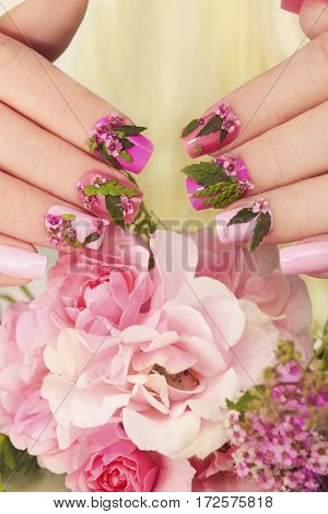 Pink pastel nails design with flowers.Nail design on female hand next to the roses.