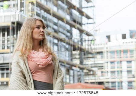Real estate concept - young woman on front of new big modern house building construction site daydreaming about new home