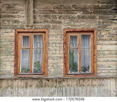 Old wooden russian house with two windows painted faded white