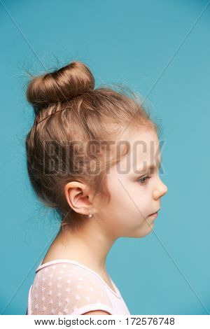 The profile of cute little girl on a blue studio background close-up