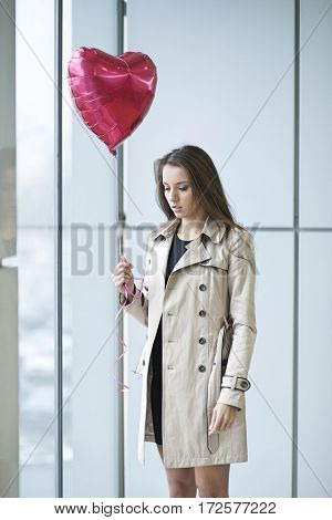Sad woman holding heart shaped balloon